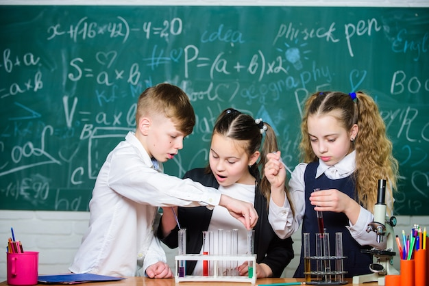액체 상태 연구. 시험관을 가진 그룹 학교 학생들은 화학 액체를 연구합니다. 학교 실험실입니다. 액체로 실험을 제공하는 소녀와 소년. 다채로운 액체 물질이 있는 시험관.