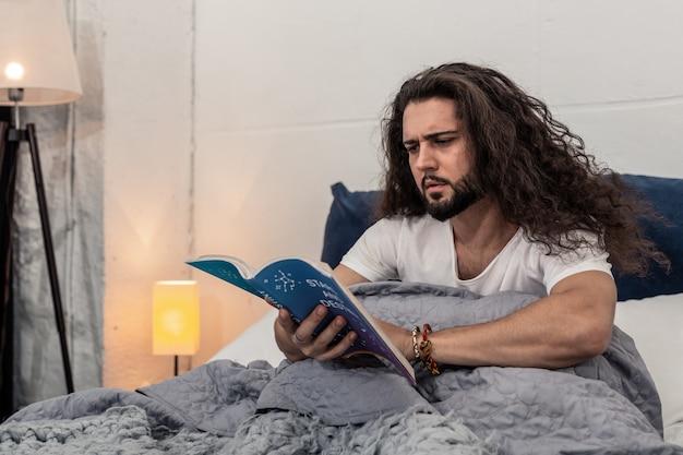 Изучение звезд. серьезный молодой человек сидит на кровати, читая книгу по астрологии