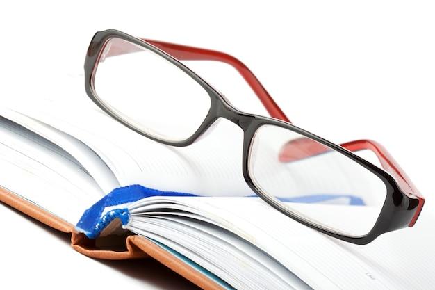 Учиться. открытая книга с очками на белом фоне