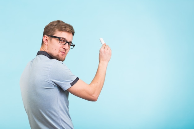 Study, students, university and college concept - young funny man holds chalk isolated on blue wall.