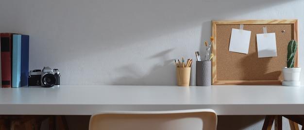 コピースペース、本、カメラ、文房具、メモリボード、装飾付きのスタディテーブル