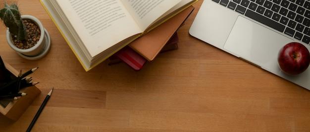 コピースペース、ラップトップ、本、文房具、木製のテーブルの装飾が付いている調査テーブル