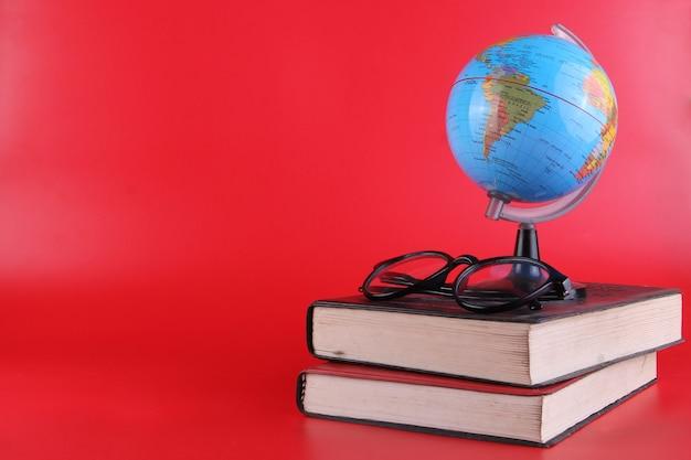 Инструменты исследования стек книг очки и глобус, изолированные на красном фоне