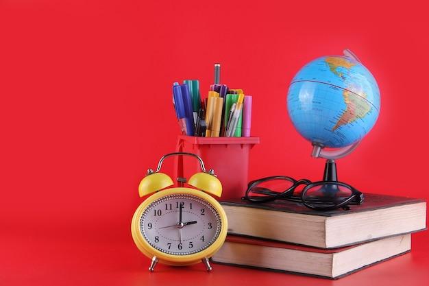 Учебные инструменты стопка книг, очки, глобус, будильник и канцелярские товары, изолированные на красном фоне