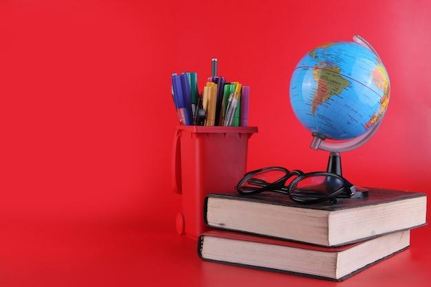 Учебные инструменты стопка книг, очки, глобус и канцелярские товары, изолированные на красном фоне