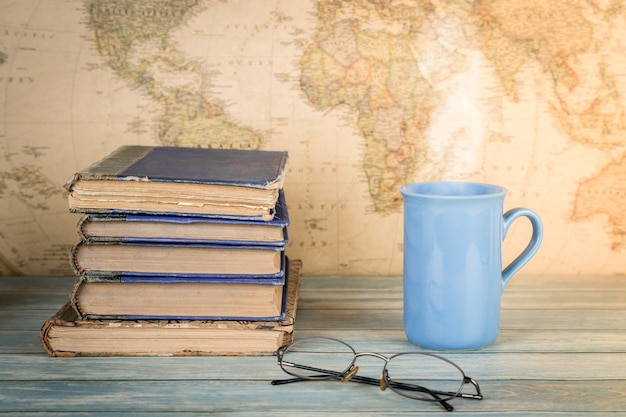 Study and travel concept. stack of old books and a cup of hot drink. map background.