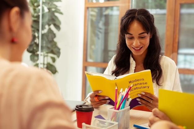 Хорошо учиться. симпатичная длинноволосая девушка с улыбкой на лице во время чтения книги
