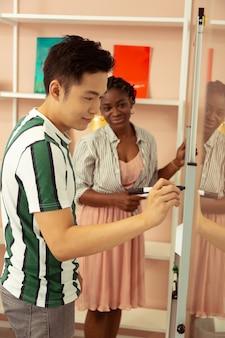 Хорошо учиться. красивый иностранный студент, изучающий английский язык, проявляет позитивный настрой