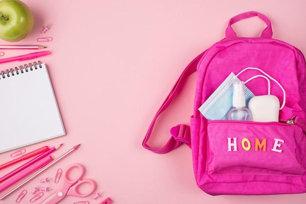 Изучение дома концепции. фотография розового рюкзака с маской, дезинфицирующим средством, мылом и розовыми канцелярскими принадлежностями, изолированных на пастельно-розовом фоне с copyspace
