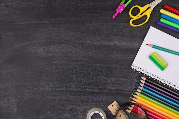 집에서 공부하는 개념. 복사 공간이 있는 칠판에 격리된 오른쪽에 배치된 다채로운 편지지의 오버헤드 뷰 사진 위