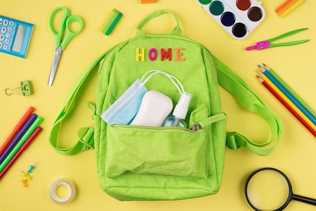 집에서 공부하는 개념. 노란색 배경에 격리된 녹색 배낭 마스크 손 소독제 비누와 다채로운 문구의 오버헤드 뷰 사진 위