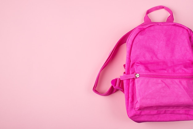 Изучение концепции. фото розового рюкзака, изолированного на пастельно-розовом фоне с copyspace