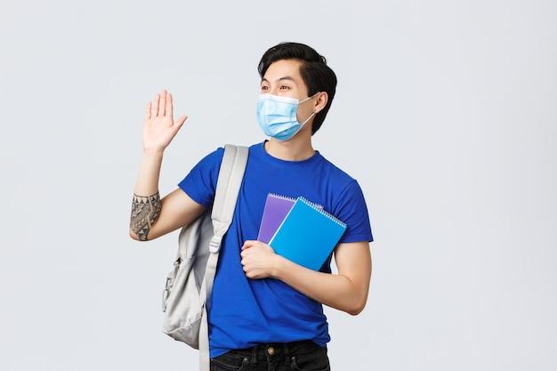 Covid-19、教育、大学生活のコンセプトの中で勉強しています。友達の大学、ヘッドキャンパス、または講義で手を振って屈託のない笑みを浮かべて男子学生、バックパックと医療用マスクを着用