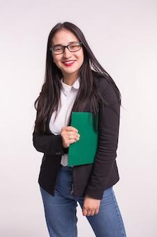 勉強、感情、人々の概念。彼女の脇の下の下にファイルと笑顔の若いブルネットの女子学生。