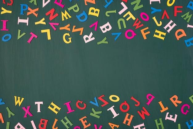 Изучение английского языка в школе концепции. вверху сверху вид сверху фото разноцветных букв с пустым центром, изолированным на зеленой доске