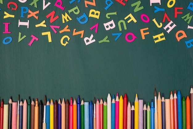 英語の概念を勉強しています。上のカラフルな文字とグリーンボードで隔離された下の鉛筆の俯瞰写真の上の上部
