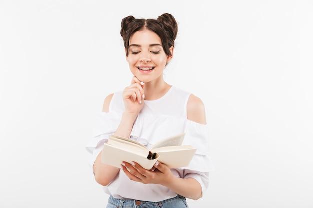 Изучающая студентка или школьница с двойной прической и брекетами, читающая книгу с улыбкой, изолированная на белом