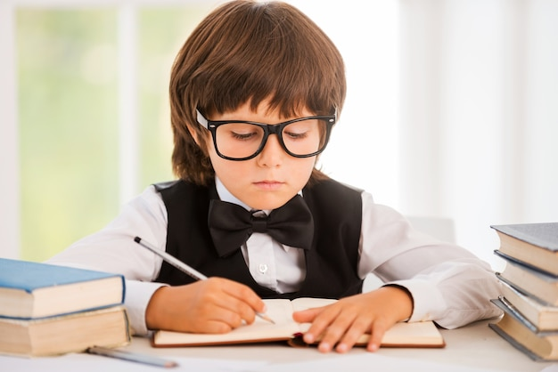 Studying hard. cute young boy making research while sitting at the desk