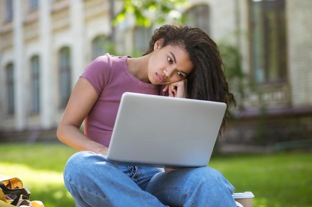 Учеба в парке. девушка в розовой футболке с ноутбуком в парке