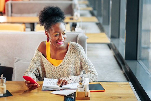 言語を勉強している外国語を勉強している間、楽しそうに感じている巻き毛の若いスマートな女性