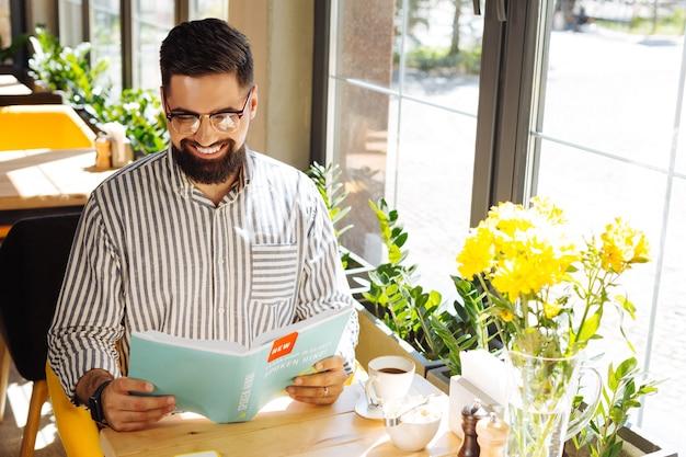 言語を勉強しています。ヒンディー語の本を読みながら笑顔の幸せなポジティブな男