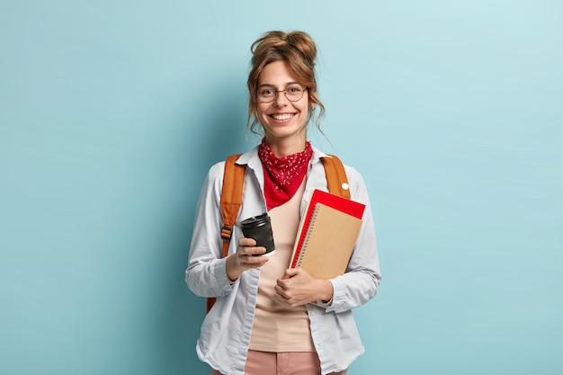 勉強、レジャー、ライフスタイルのコンセプト。ヨーロッパの女の子は誠実な笑顔を持って、良い気分で大学から戻って、コーヒーを飲みます