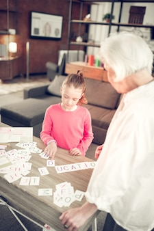 Studying letters. dark-haired preschool girl studying letters with loving and caring granny