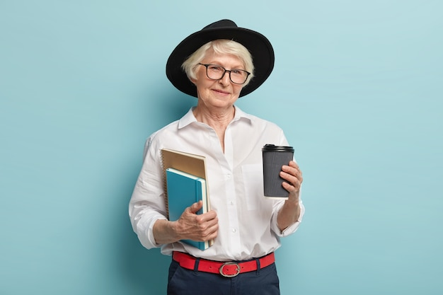 Studiare in vecchiaia. piacevole donna rugosa in copricapo nero, tiene due taccuini, caffè da asporto, si prepara a tenere lezioni, isolato su muro blu. persone, pensione e concetto di bere