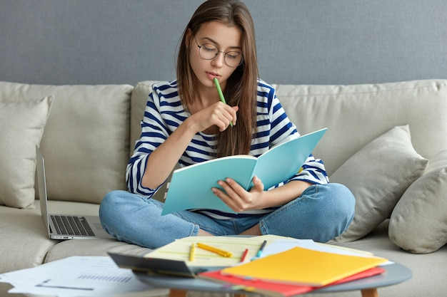 Studying online concept. serious young woman being busy with remote freelance project, sits at comfortable sofa, writes notes, holds textbook, use laptop computer at home with wireless internet