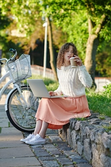 Studying remotely. a young girl with a laptop sitting onthe bench in the park