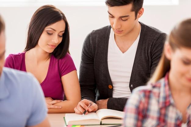 一緒に勉強します。教室に座って一緒に勉強している元気な学生