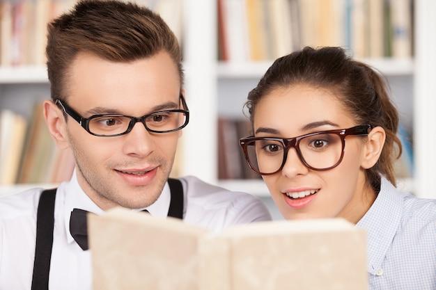 Учиться вместе - это весело. взволнованная пара молодых ботаников в очках вместе читает книгу, сидя в библиотеке