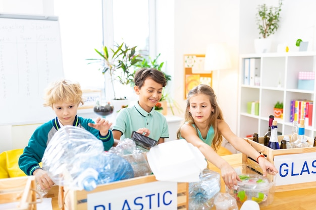 Изучение сортировки мусора. умные сияющие дети изучают сортировку мусора на уроке экологии в школе