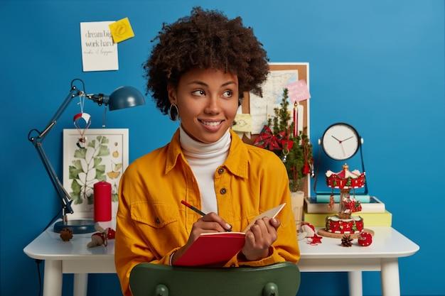 勉強、冬時間、休日の概念。アフロの髪の満足した思いやりのある女性は赤いメモ帳にメモを書き留め、クリスマスイブの前にやるべきリストを作ります
