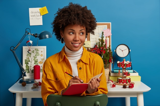 Studying, winter time, holidays concept. satisfied thoughtful woman with afro hair writes down notes in red notepad, makes list to do before christmas eve