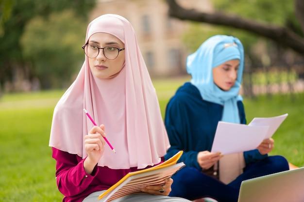친구와 공부. 분홍색 hijab와 친구와 함께 공부하는 안경을 착용하는 이슬람 학생