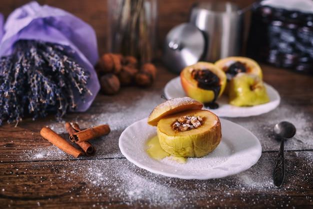 ナッツ、蜂蜜、白いデザートプレート、暗い背景の木にチョコレートを詰めた焼きりんご。クリスマス甘い。健康的な食事のコンセプト。