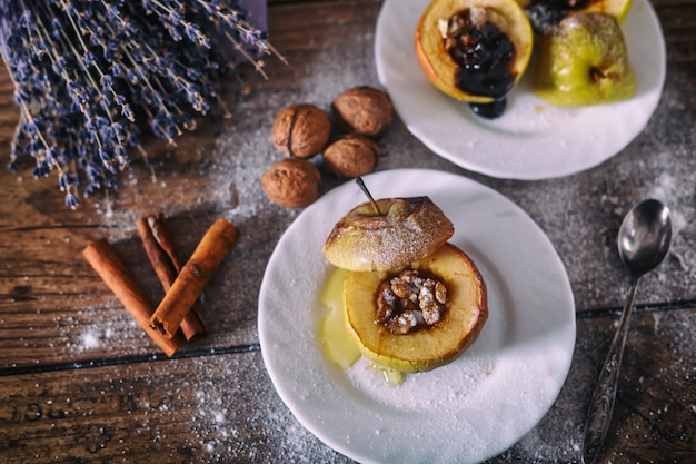 Stuffed baked apple with nuts, honey and chocolate on white dessert plates, dark wooden background. christmas sweet. healthy eating concept.