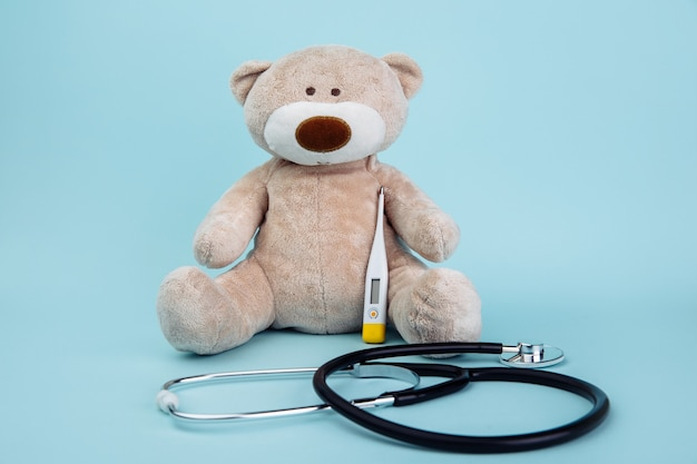 Stuffed bear animal presented as a pediatrician holding a thermometer isolated on blue.