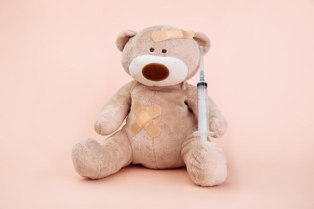 Чучело медведя со шприцем, изолированным на розовом