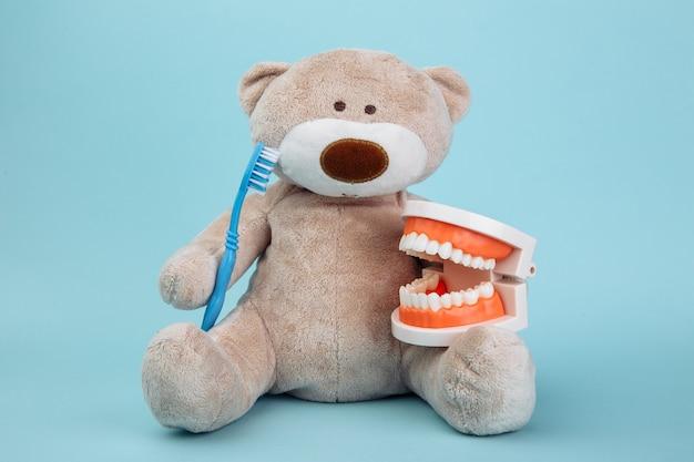 Чучело медведя с зубной щеткой как символ концепции детской стоматологии, изолированной на синем.