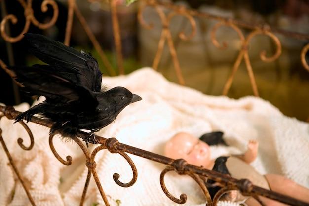 Stuffed blackbird and baby doll in antique crib