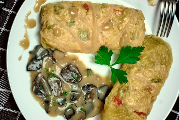 Stuffed cabbage rolls with rice and chicken meat in forest mushroom sauce.