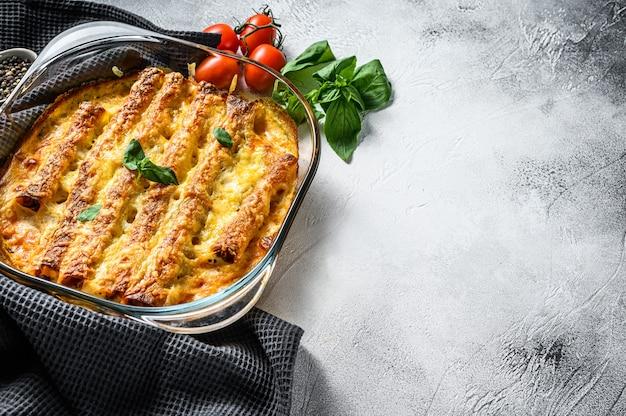 Каннеллони фаршированные соусом бешамель. макароны запеченные с мясом говядины, сливочным соусом, сыром. вид сверху. копировать пространство