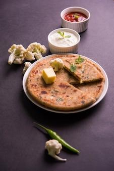 속을 채운 콜리플라워 또는 고비 파라타는 인도의 평평한 빵입니다. 변덕스러운 배경 위에 커드와 토마토 케첩을 그릇에 담아 제공되는 인도 북부에서 가장 좋아하는 아침 또는 점심 메뉴