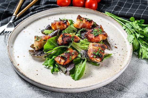 Фаршированные куриные грудки, филе в беконе с зеленым салатом. вид сверху