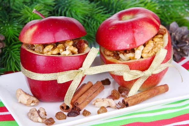 テーブルの上のナッツとレーズンのぬいぐるみクリスマスりんごのクローズアップ