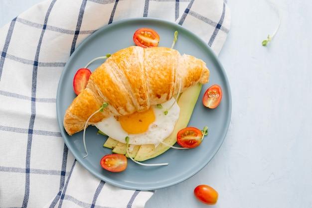 Фаршированный круассан с авокадо, яйцом омлет и свежими овощами