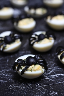Stuffed deviled eggs with black olive spiders for halloween
