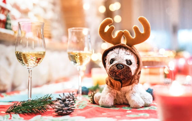 Stuffed dog toy wearing reindeer ears sitting upon table near champagne glasses on christmas holidays background